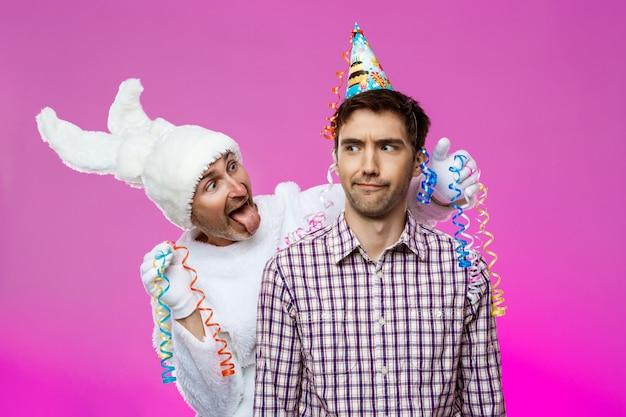 Hombre borracho y conejo en la fiesta de cumpleaños sobre la pared púrpura.