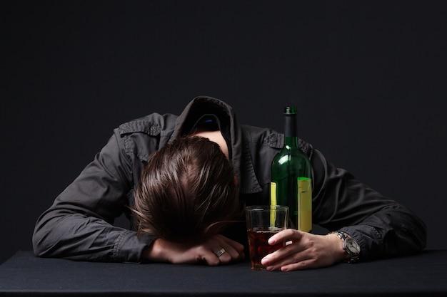 Hombre borracho durmiendo en la mesa con una copa de vino en la mano