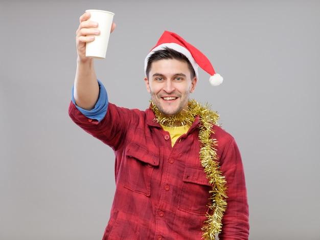Hombre borracho joven divertido que lleva el sombrero de papá noel que sostiene una taza de papel