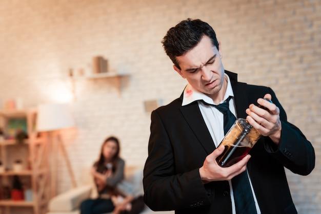 Hombre borracho en traje bebe alcohol en casa