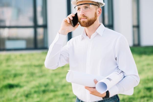 Hombre con borradores hablando por teléfono inteligente