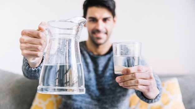 Hombre borroso mostrando jarra y vaso