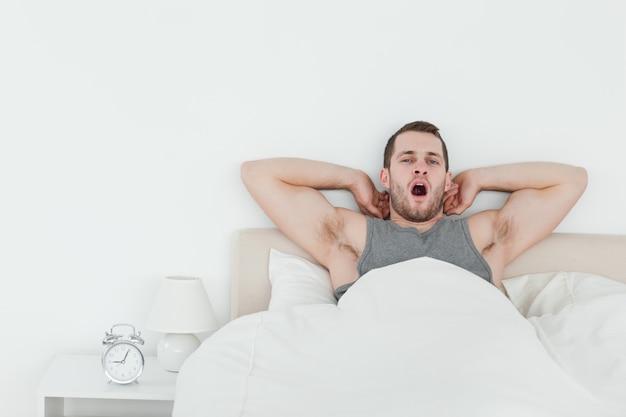 Hombre bostezando mientras se despierta