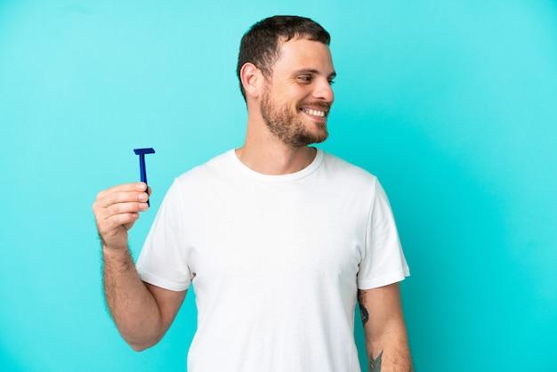 Hombre brasileño afeitándose la barba aislado sobre fondo azul mirando de lado