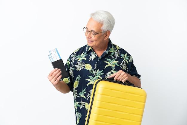 Hombre brasileño de mediana edad aislado sobre fondo blanco en vacaciones con maleta y pasaporte
