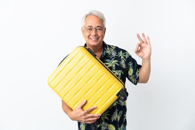 Hombre brasileño de mediana edad aislado sobre fondo blanco en vacaciones con maleta de viaje y haciendo el signo de ok