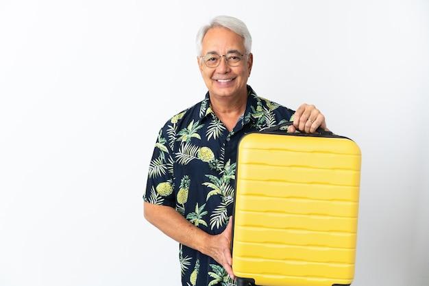Hombre brasileño de mediana edad aislado sobre fondo blanco en vacaciones con maleta de viaje