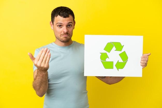 Hombre brasileño sobre fondo púrpura aislado sosteniendo un cartel con el icono de reciclaje y haciendo el gesto de venir