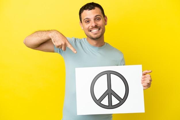 Hombre brasileño sobre fondo púrpura aislado sosteniendo un cartel con el símbolo de la paz y apuntando