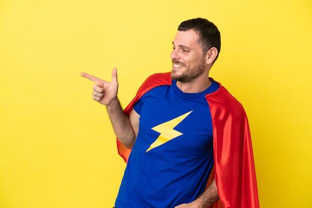 Hombre brasileño de superhéroe aislado sobre fondo amarillo que señala el dedo hacia un lado y presenta un producto