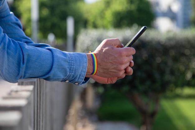 Hombre con brazalete de bandera gay sosteniendo un teléfono inteligente
