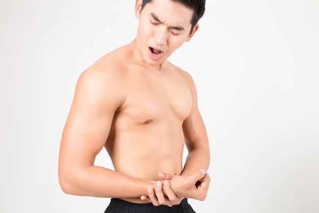 Hombre con brazo sintiendo dolor. foto de estudio con fondo blanco. concepto de fitness y salud