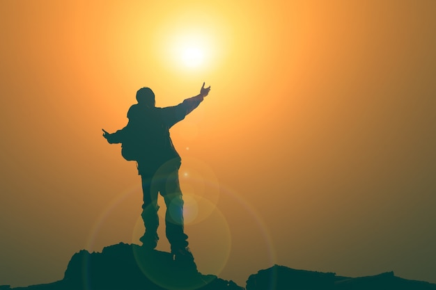 Hombre con los brazos extendidos hacia el cielo al amanecer.