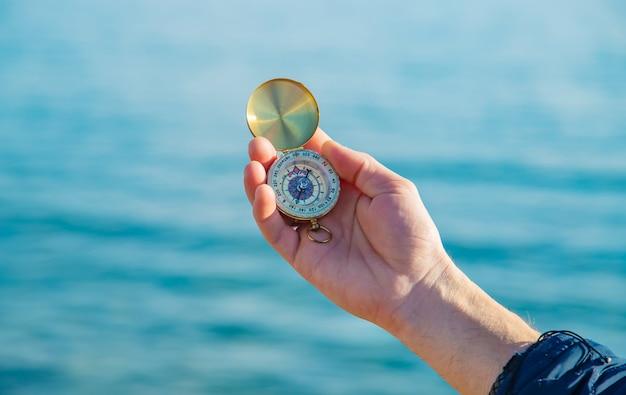 Un hombre con una brújula en sus manos cerca del mar. enfoque selectivo.