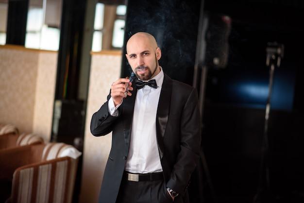 Un hombre brutal en un abrigo de vestir fuma un cigarro.