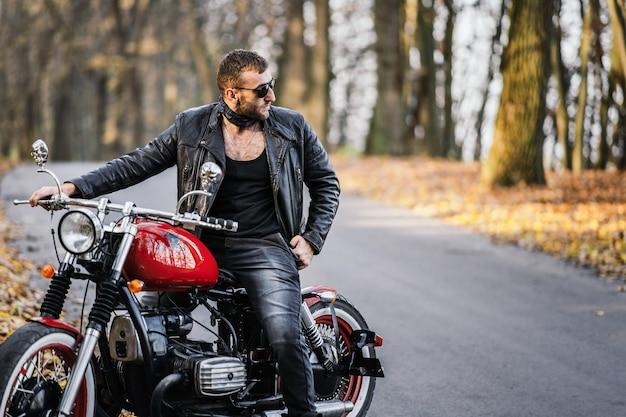 Hombre brutal barbudo con gafas de sol y chaqueta de cuero sentado en una motocicleta en la carretera en el bosque