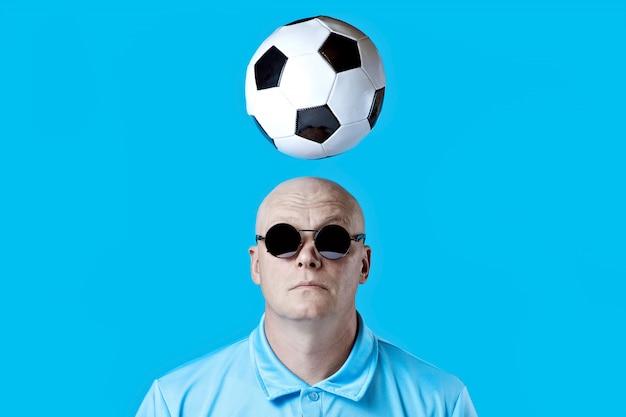 Hombre brutal calvo con gafas redondas oscuras con reflejos en azul