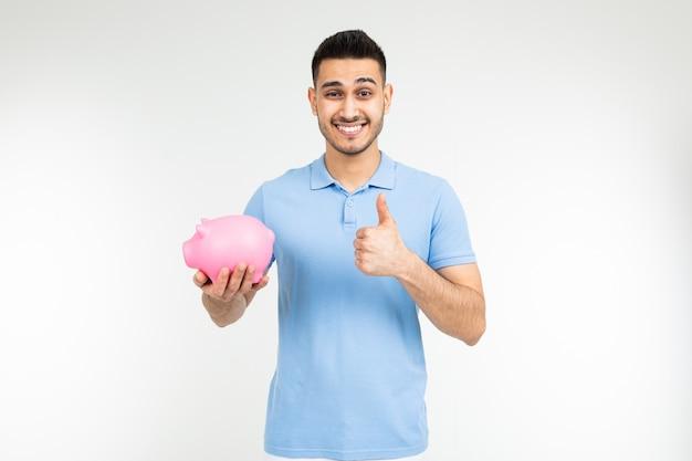 Hombre brutal con una camisa azul sostiene una alcancía y muestra una súper clase en un blanco con espacio de copia