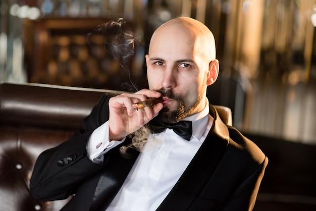 Un hombre brutal con una chaqueta de vestir fuma un puro.