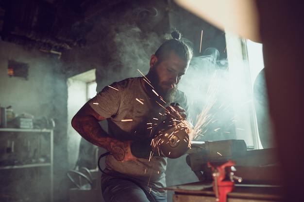 Hombre brutal guapo con barba reparando una motocicleta en su garaje trabajando con una sierra circular. en el garaje muchas chispas y humo de serrar
