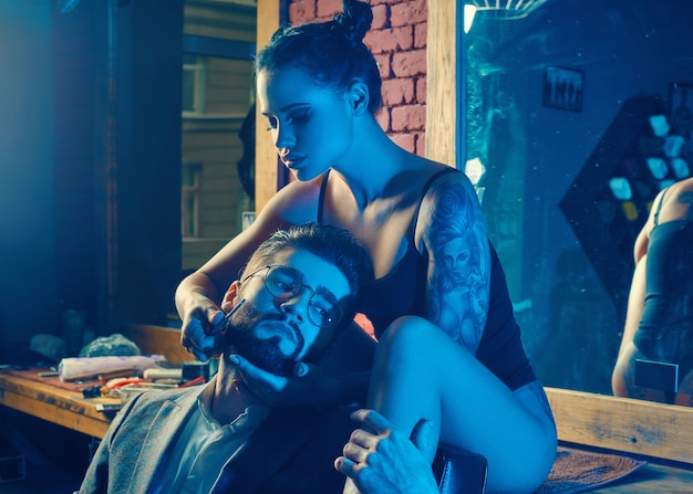 Hombre brutal en traje elegante y sexy chica con tatuaje