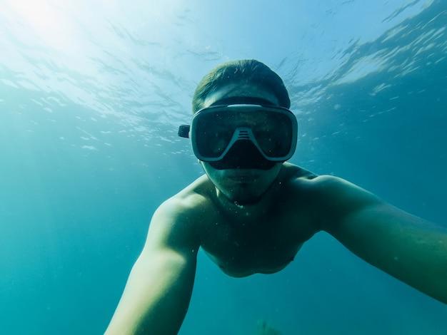 Hombre buceando y tomando una selfie bajo el agua