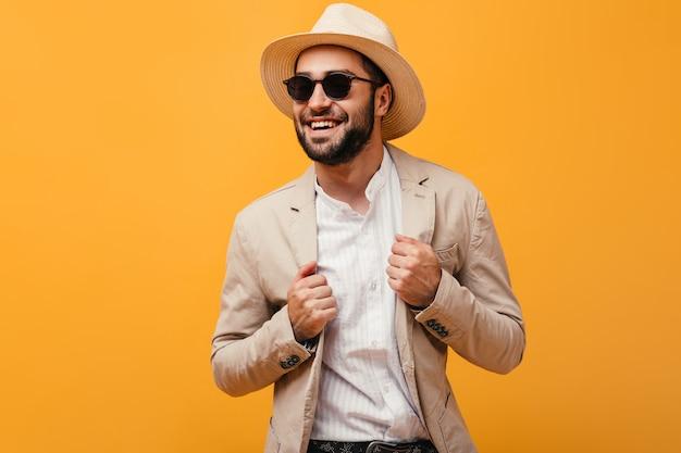 Hombre de buen humor riendo en pared naranja