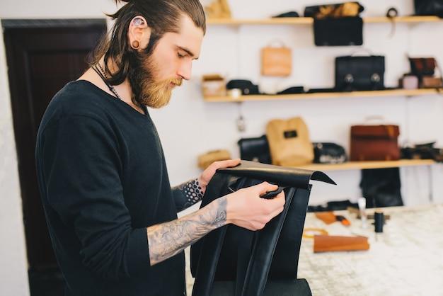 El hombre busca una mochila de cuero de calidad.
