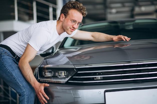 Hombre buscando un coche en una sala de exposición de coches.