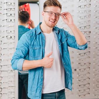 Hombre buscando gafas nuevas en óptico