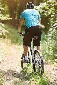Hombre cabalgando por una carretera extrema en el bosque