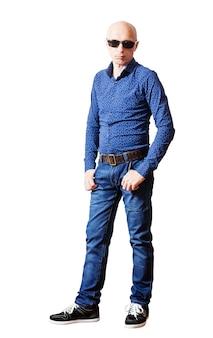 Hombre cabeza rapada en camisa de gafas de sol y pantalones vaqueros azules