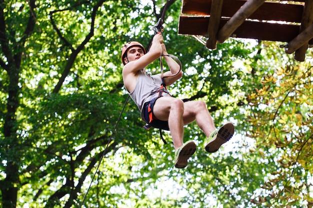 El hombre cae en la cuerda en un parque de entretenimiento