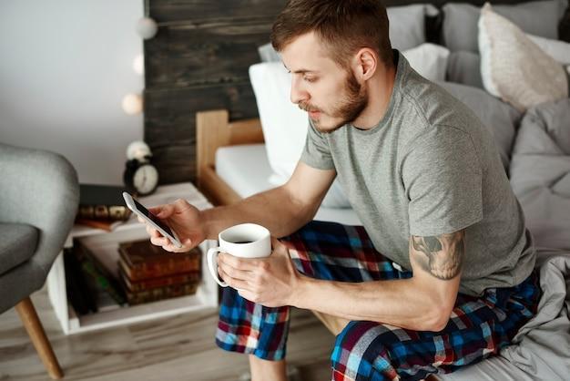 Hombre con café y mensajes de texto de teléfono móvil