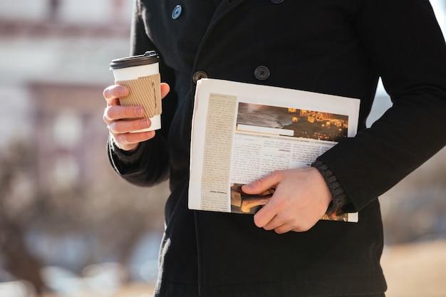 Hombre con café y periódico caminando en la ciudad.
