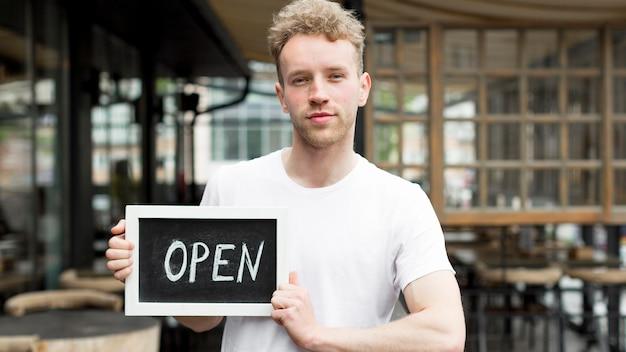 Hombre en cafetería con cartel abierto