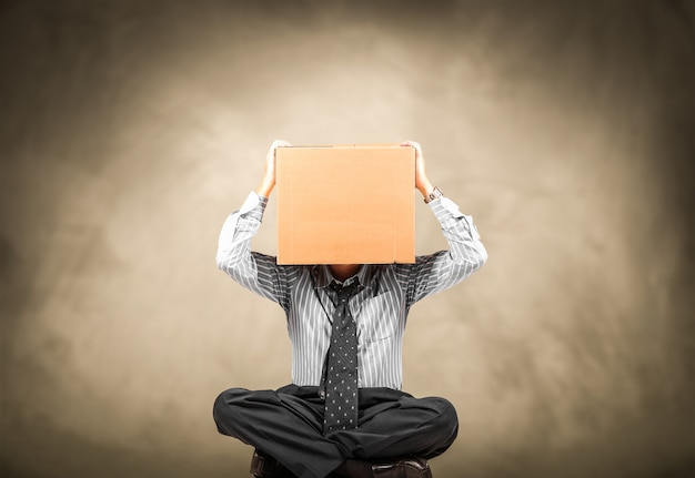 Hombre con una caja de cartón en la cabeza.