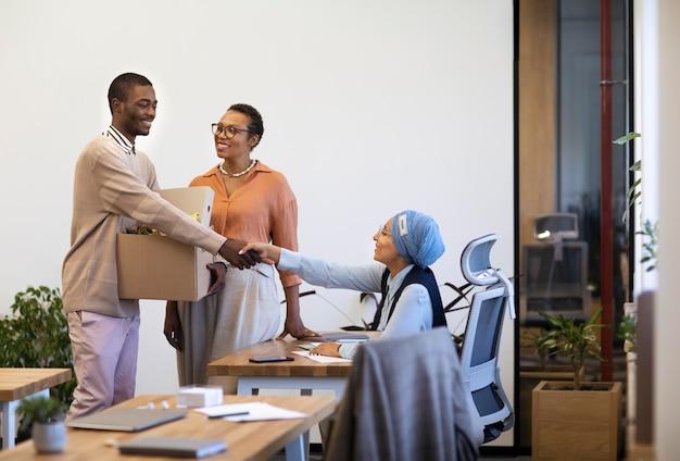 Hombre con caja de pertenencias que se presenta a compañeros de trabajo en su nuevo trabajo