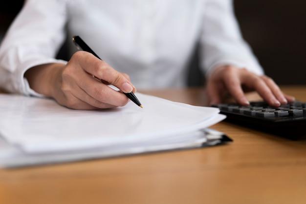Hombre calculando y escribiendo cerca