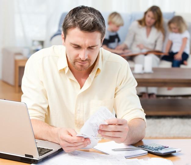 Hombre calculando sus cuentas mientras su familia está en el sofá