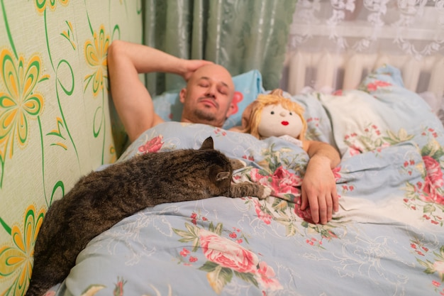 Hombre calvo adulto durmiendo en la cama y abrazando muñeca de tela y gato perezoso.