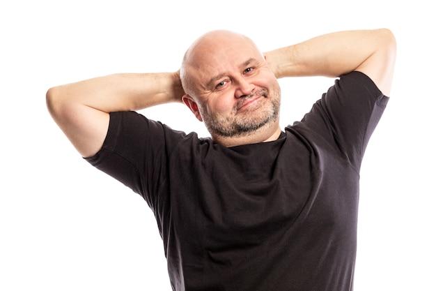 Hombre calvo adulto con las manos detrás de la cabeza está sonriendo. aislado en un fondo blanco.