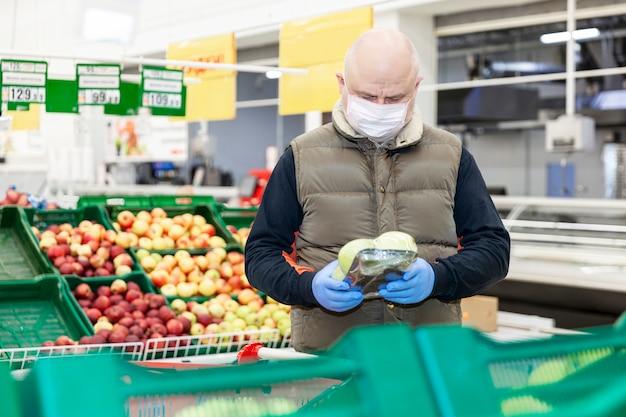 Hombre calvo adulto en una máscara médica y guantes elige frutas en un supermercado. alimentación saludable y vegetarianismo. autoaislamiento durante la pandemia de coronavirus.