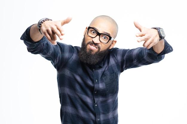 Hombre calvo afroamericano agresivo enojado con barba en vasos apuntando con ambas manos