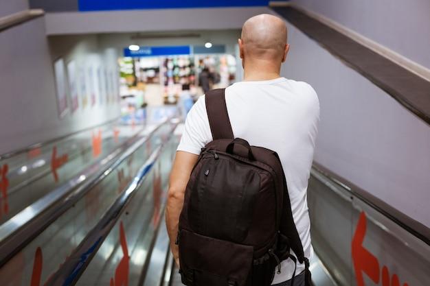 Hombre calvo camina por las escaleras mecánicas con una mochila al centro comercial