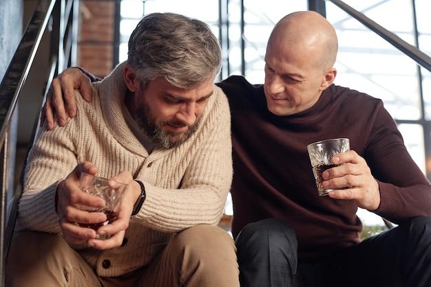 Hombre calvo en cuello alto sentado con vaso de whisky en las escaleras y apoyo amigo en depresión