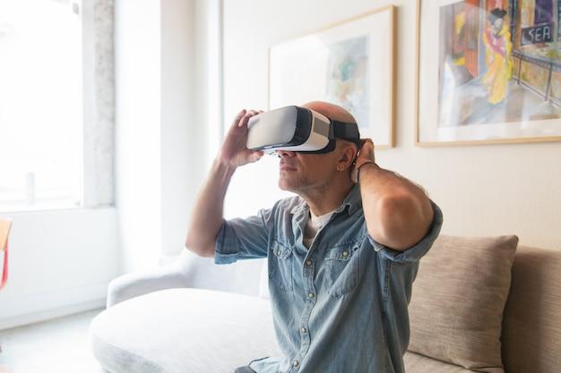 Hombre calvo disfrutando de la experiencia de realidad virtual en casa