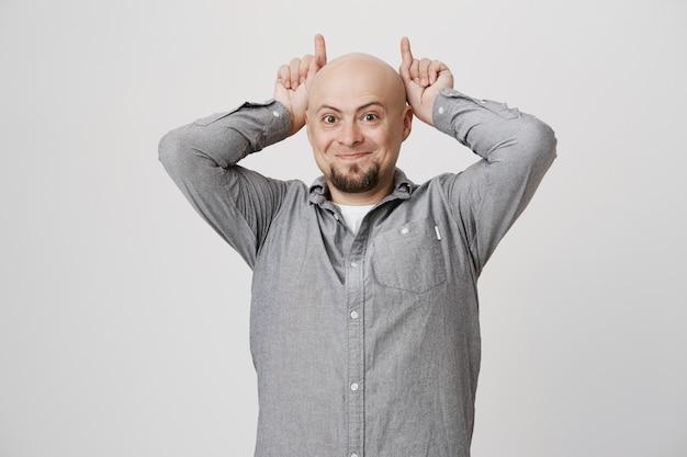 Hombre calvo gracioso tonto mostrando cuernos detrás de la cabeza
