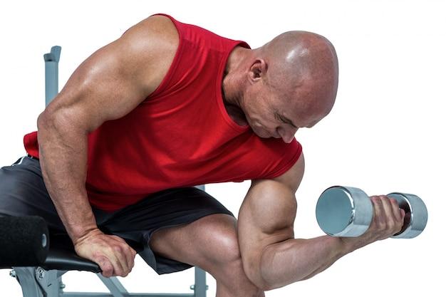 Hombre calvo haciendo ejercicio con pesas mientras está sentado en el press de banca