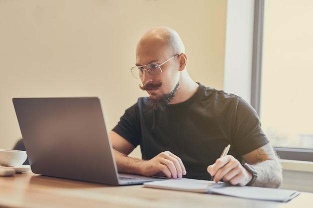 Hombre calvo joven que trabaja en la computadora portátil sentados en el escritorio estudiando haciendo algo notas aprendizaje a distancia